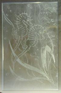 Sklo s vybroušeným obrazem dvou mořských koníků